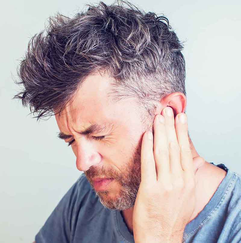 Man holding his ear trying to stop the ringing in his ear he is experiencing.