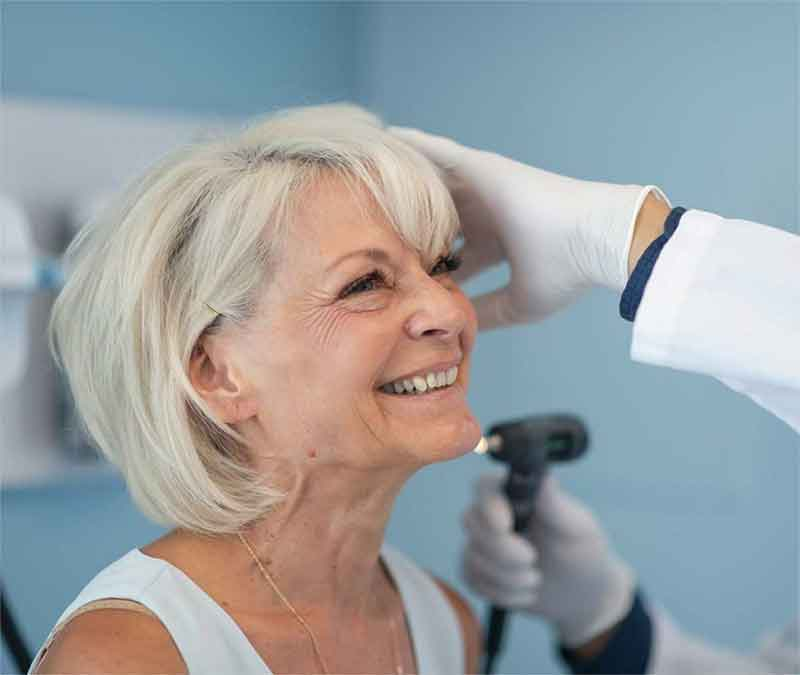 Woman having her ears examined by a hearing expert